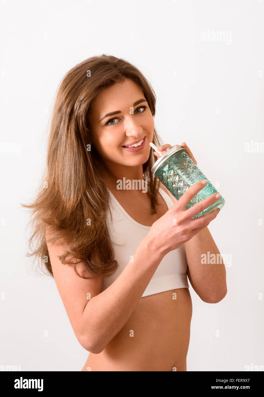 Young female with smoothie jar smiling at camera - Stock Image