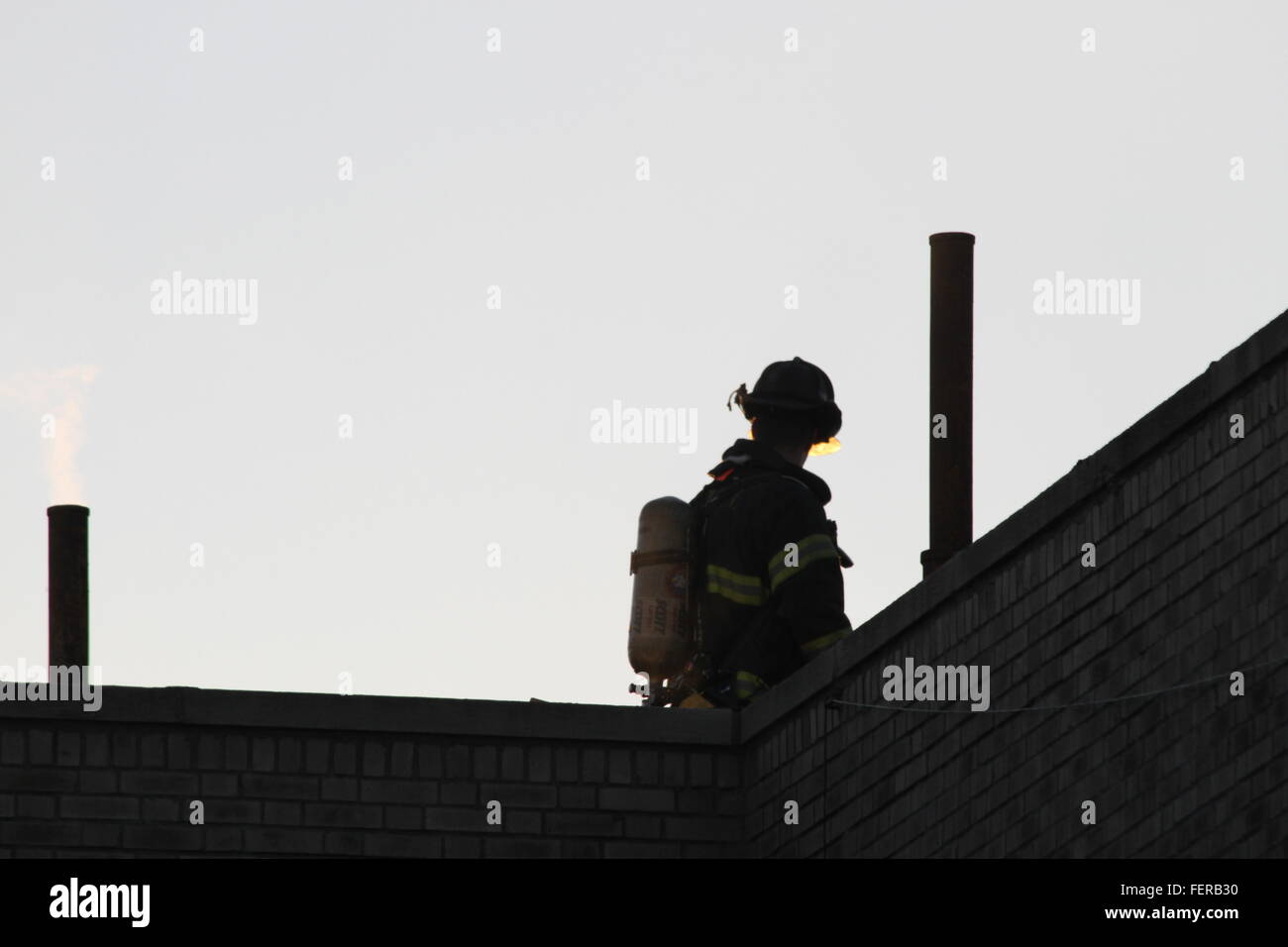 Rear View Of Fireman In Protective Suit - Stock Image
