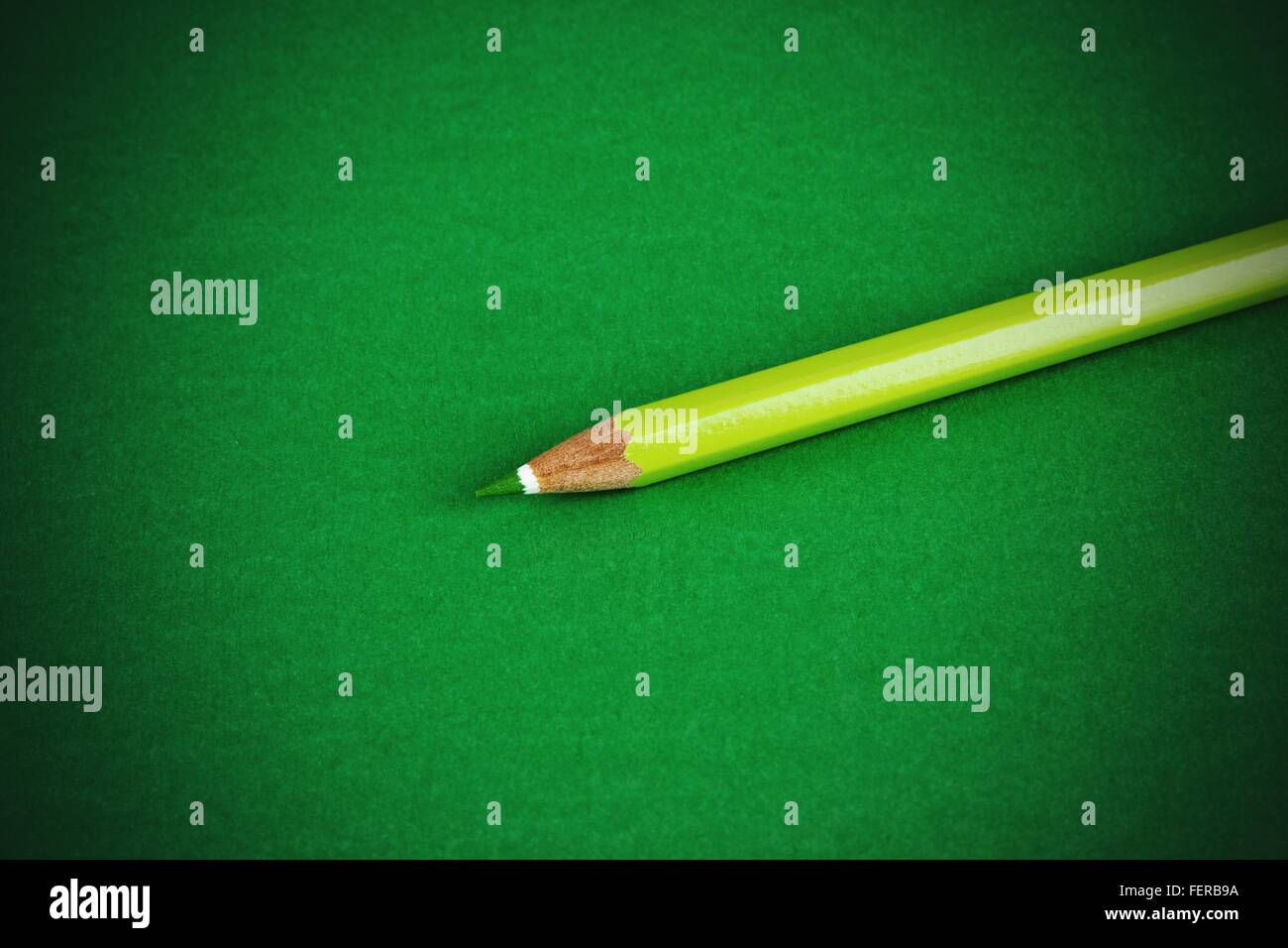 Green Colored Pencil Against Colored Background - Stock Image