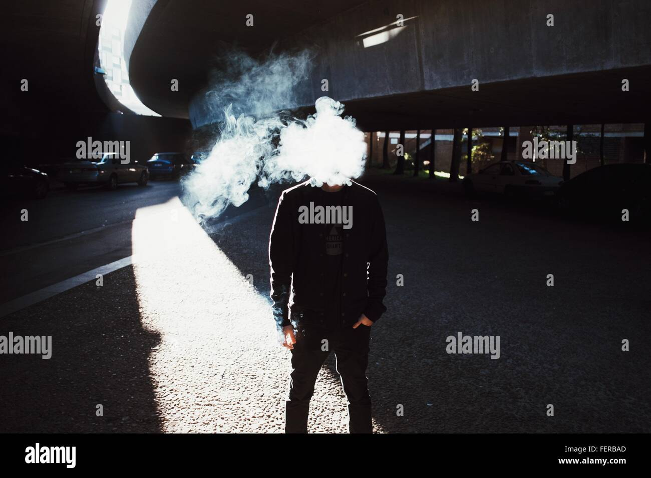 67eae9e9c58 Man Face Covered With Smoke Standing Below Bridge - Stock Image