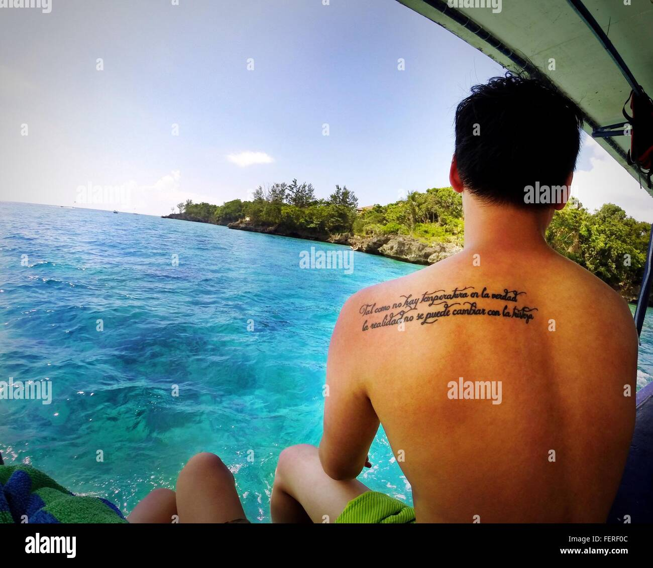 Rear View Of Shirtless Man With Tattoo On Back At Sea - Stock Image