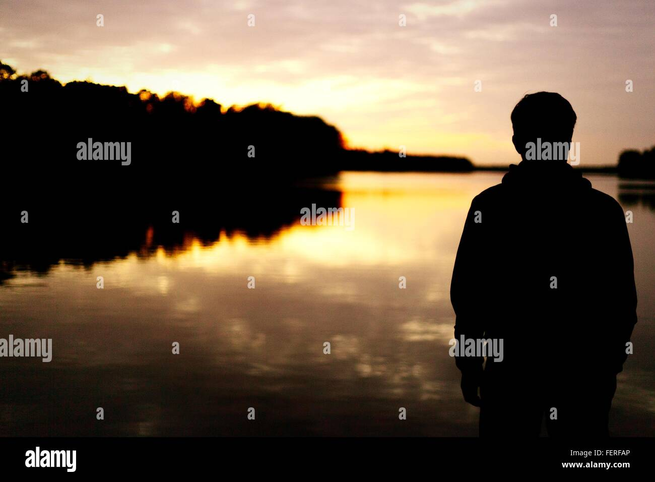 Rear View Of Silhouette Man Standing In Front Of Lake During Sunset - Stock Image