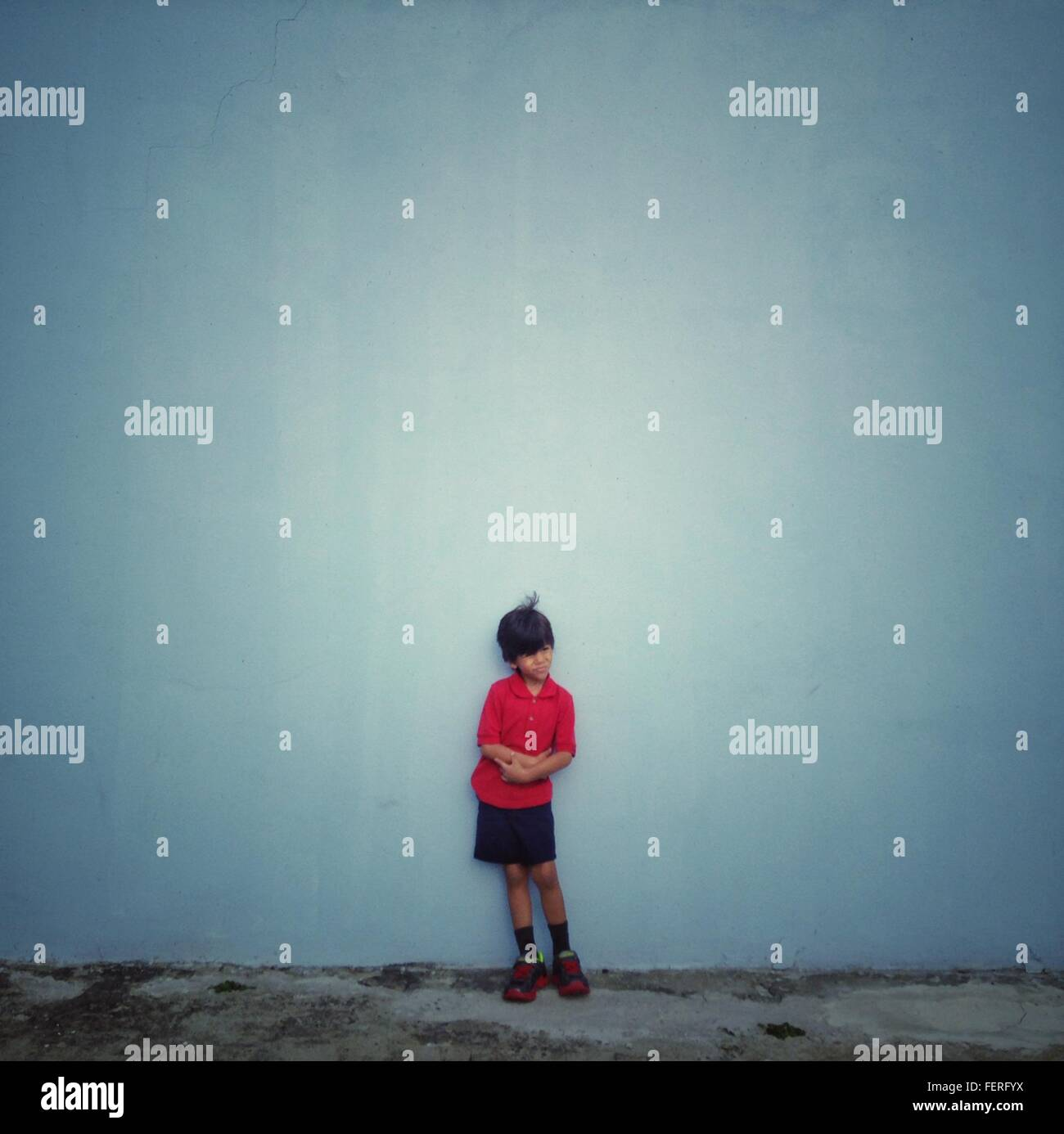Full Length Of Boy Standing Against Wall While Looking Away - Stock Image