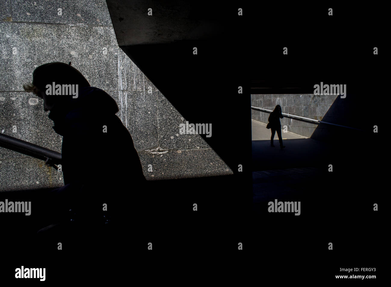 High Angle View Of Silhouette Women Walking In Subway On Sunny Day - Stock Image