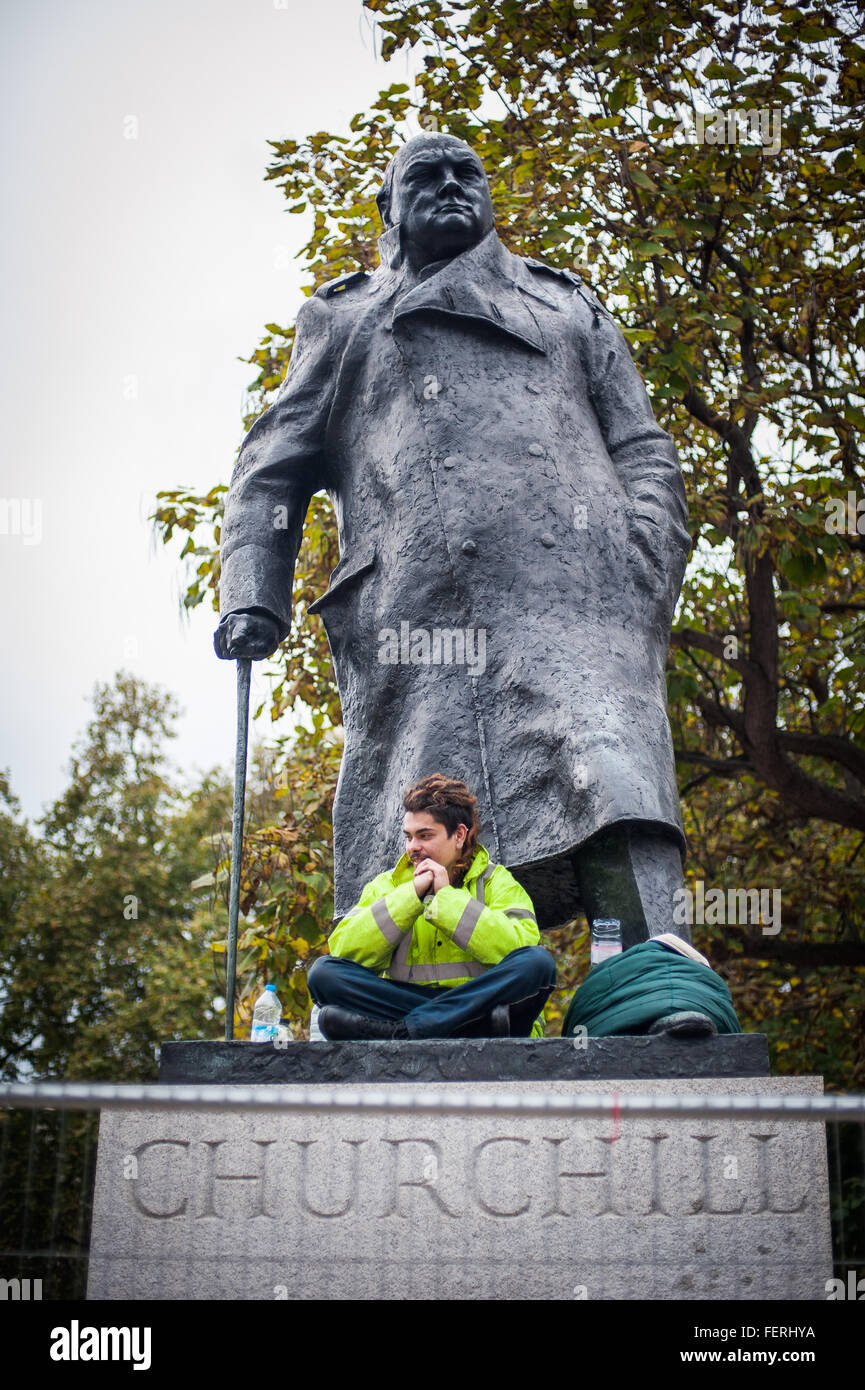Anti-capitalist protester sits on Churchill statue for 28-hour stint against police orders - Stock Image
