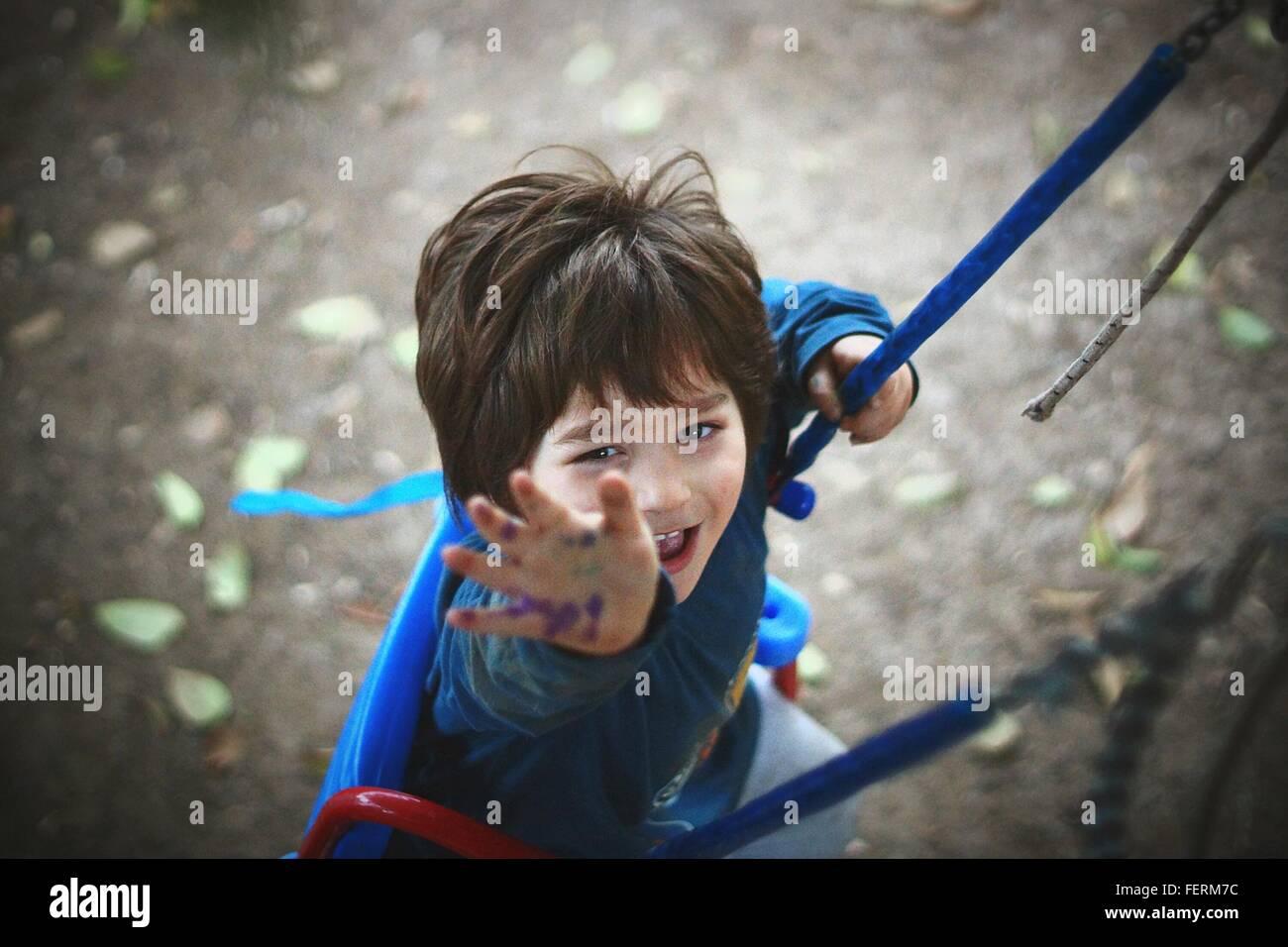 Portrait Of Boy Enjoying Swing In Park - Stock Image
