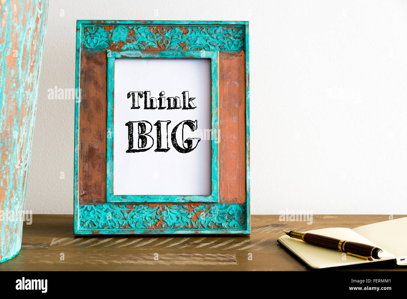 Vintage photo frame on wooden table over white wall background with motivational message THINK BIG , copy space - Stock Image