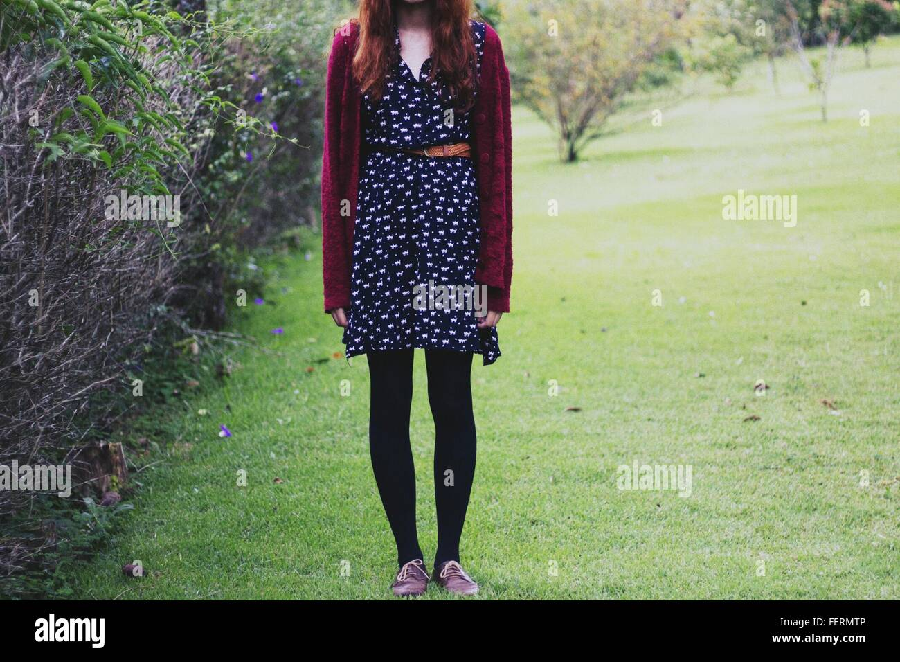 Low Section Of Young Woman On Grassy Field In Park - Stock Image