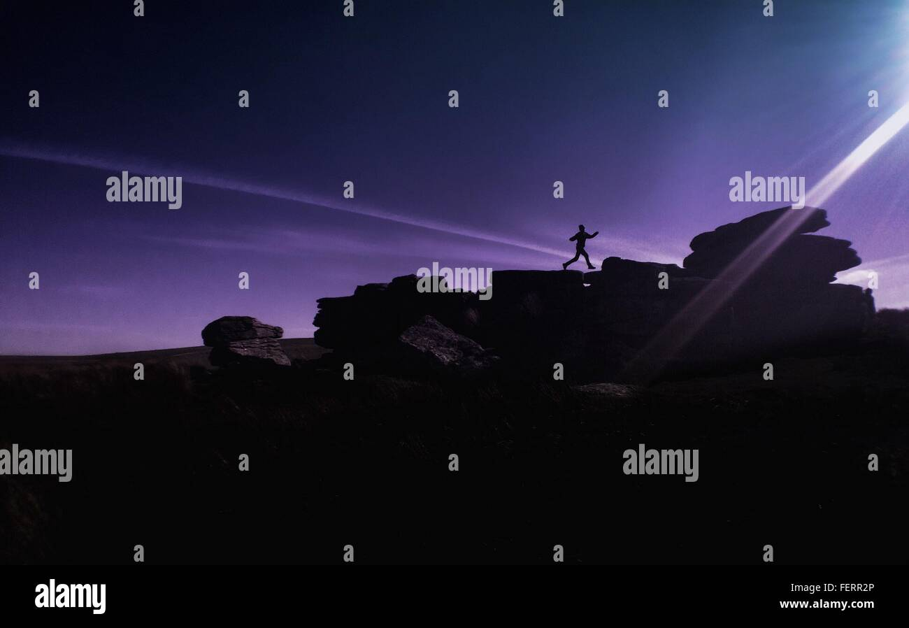 Silhouette Person Running On Rocks Against Sky At Dartmoor National Park - Stock Image