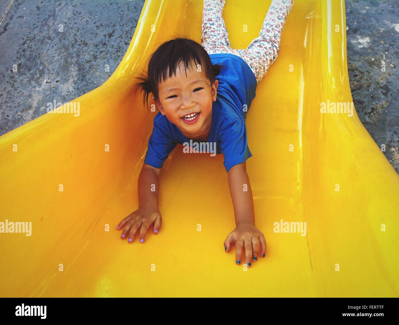 Portrait Of Happy Girl Playing On Yellow Slide In Playground - Stock Image