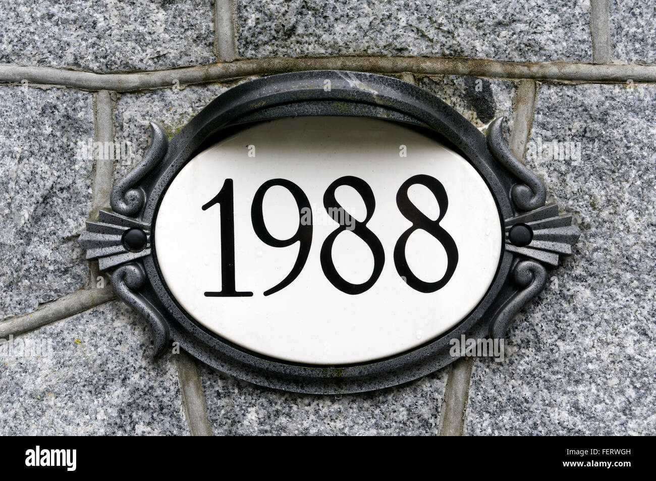 1988 house number on ornate oval plaque - Stock Image