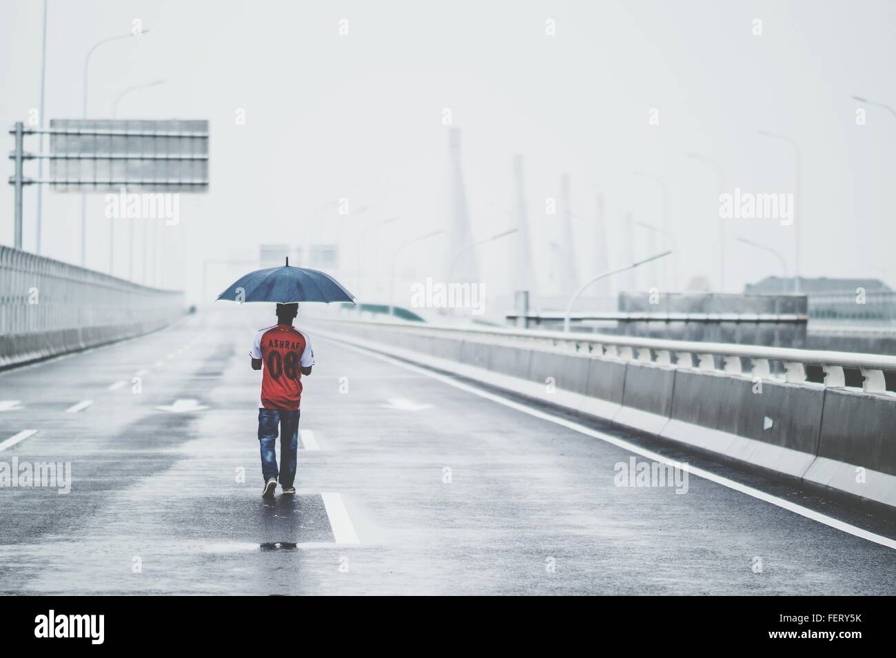 Rear View Of Man Carrying Umbrella While Walking On Road During Rainy Season - Stock Image