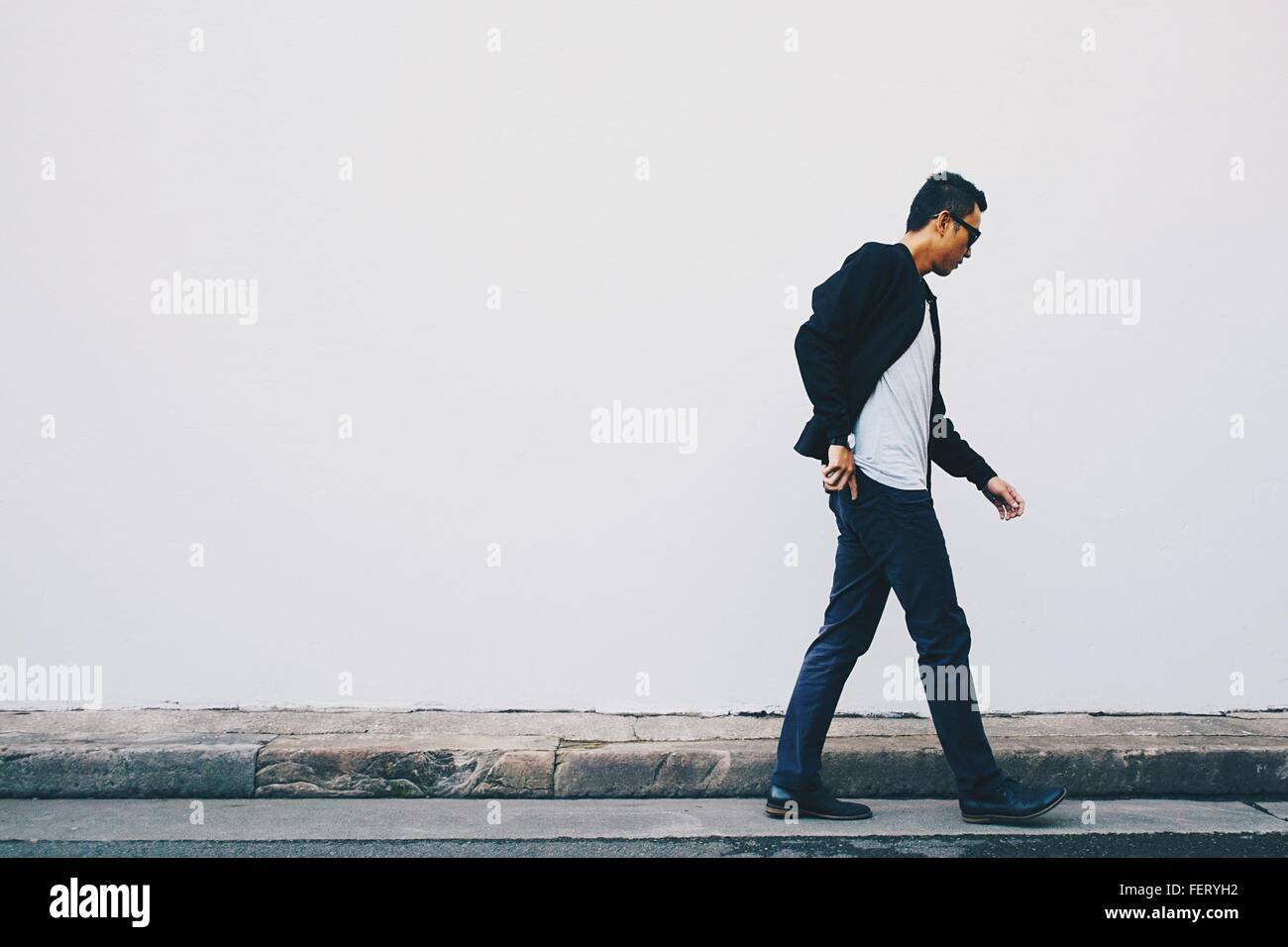 Young Man Walking On Street Against White Wall - Stock Image