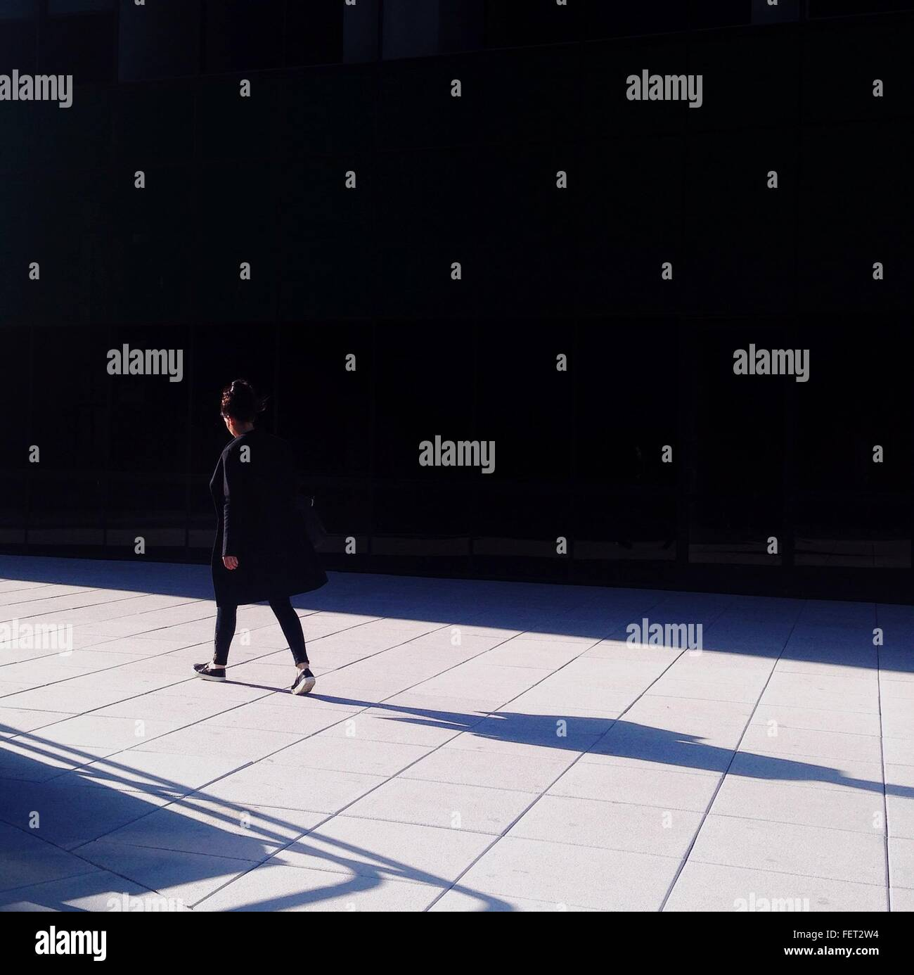 Side View Of A Woman Walking On Road - Stock Image