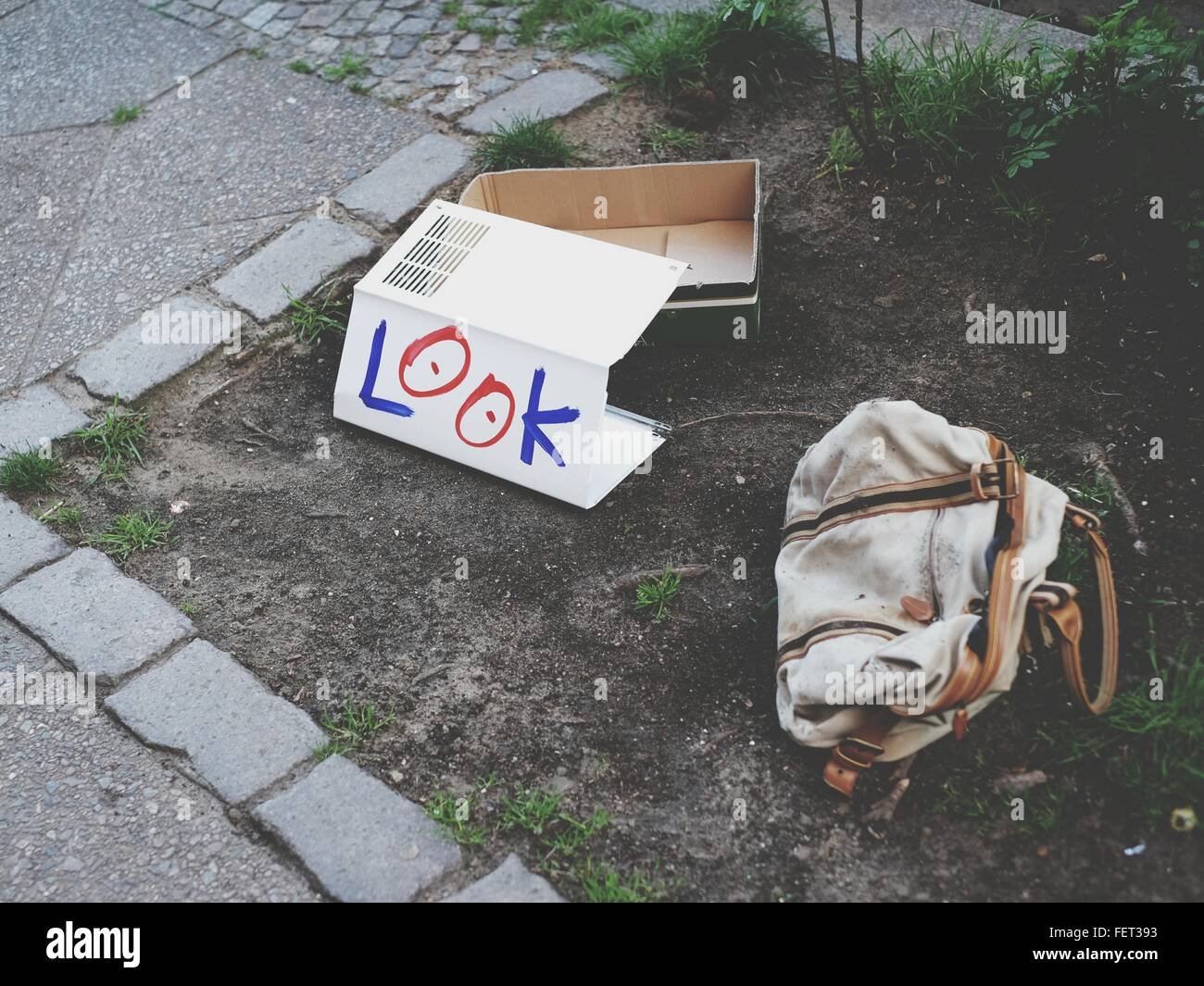 Look Written On Cardboard Paper By Abandoned Bag - Stock Image