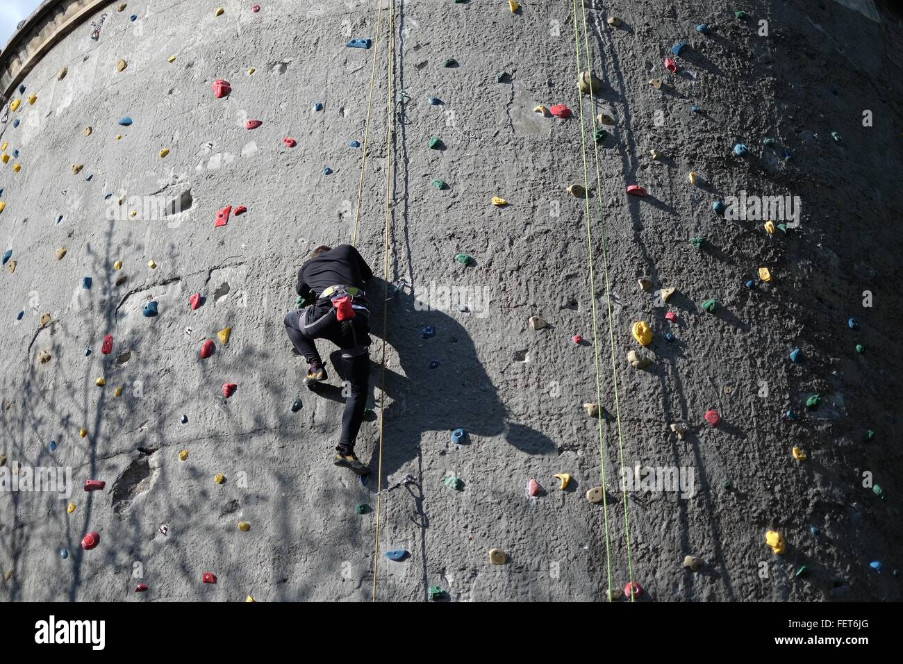 Low Angle View Of Man On Climbing Wall - Stock Image