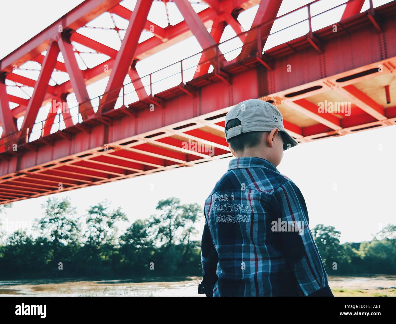 Rear View Of Boy Standing By Bridge Against Sky Stock Photo