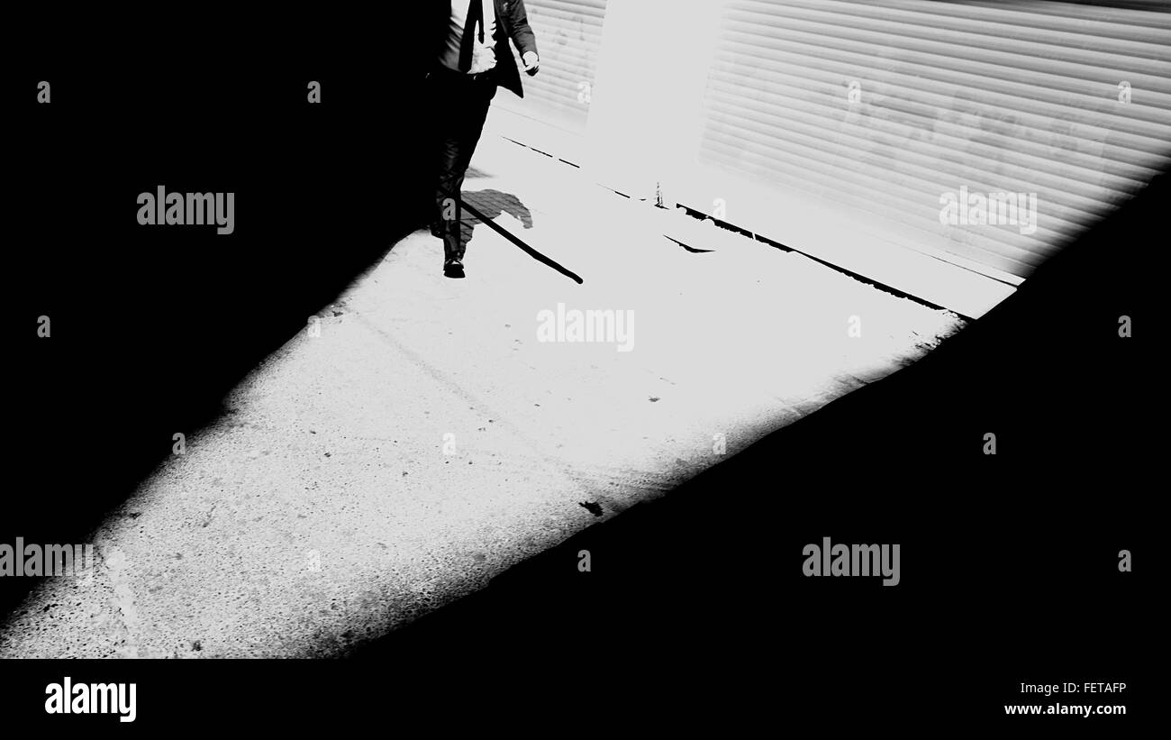 Man In Formalwear Walking On Street By Shutter - Stock Image