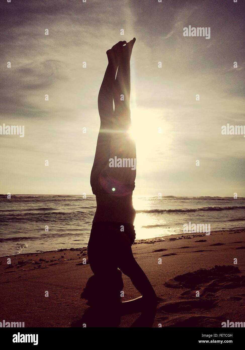 Silhouette Woman Performing Headstand On Beach - Stock Image