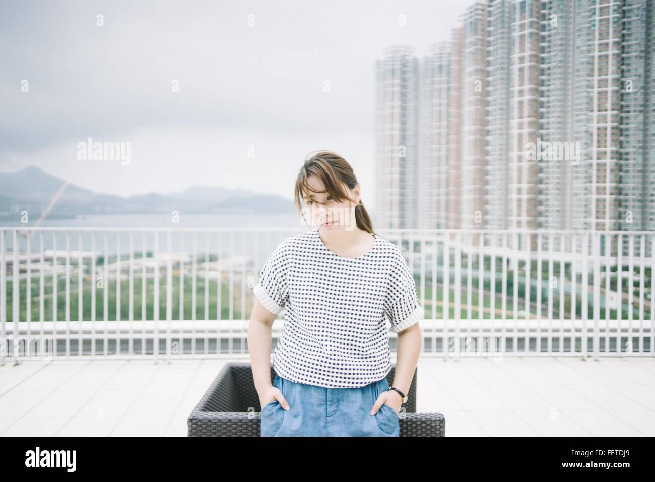 Thoughtful Woman Standing Against Modern Buildings - Stock Image
