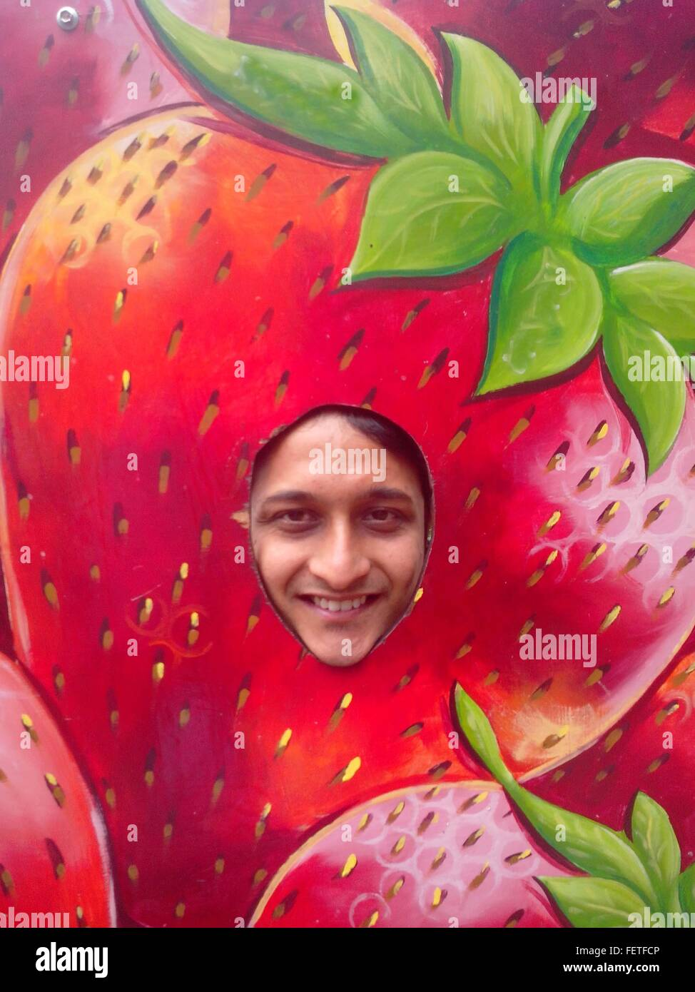 Portrait Of Man In Strawberry-Shaped Decoration - Stock Image