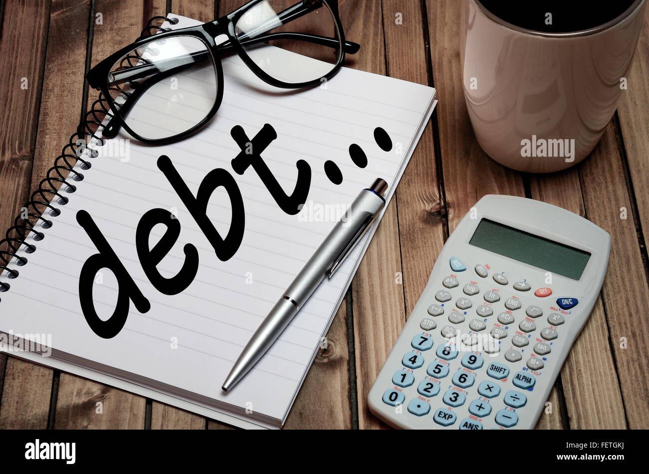 Debt word on notepad closeup - Stock Image