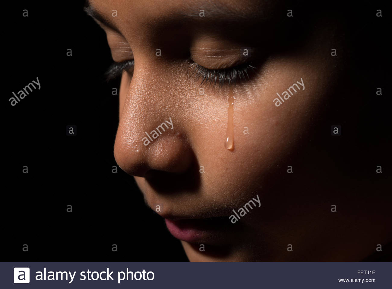 Young Asian child, could be a girl or boy crying with tears running down the face. - Stock Image