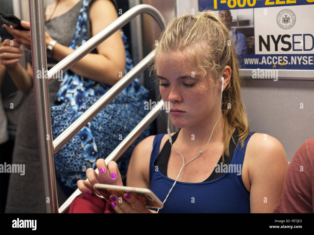 A young woman uses her phone with earbuds on the subway in New York City. - Stock Image