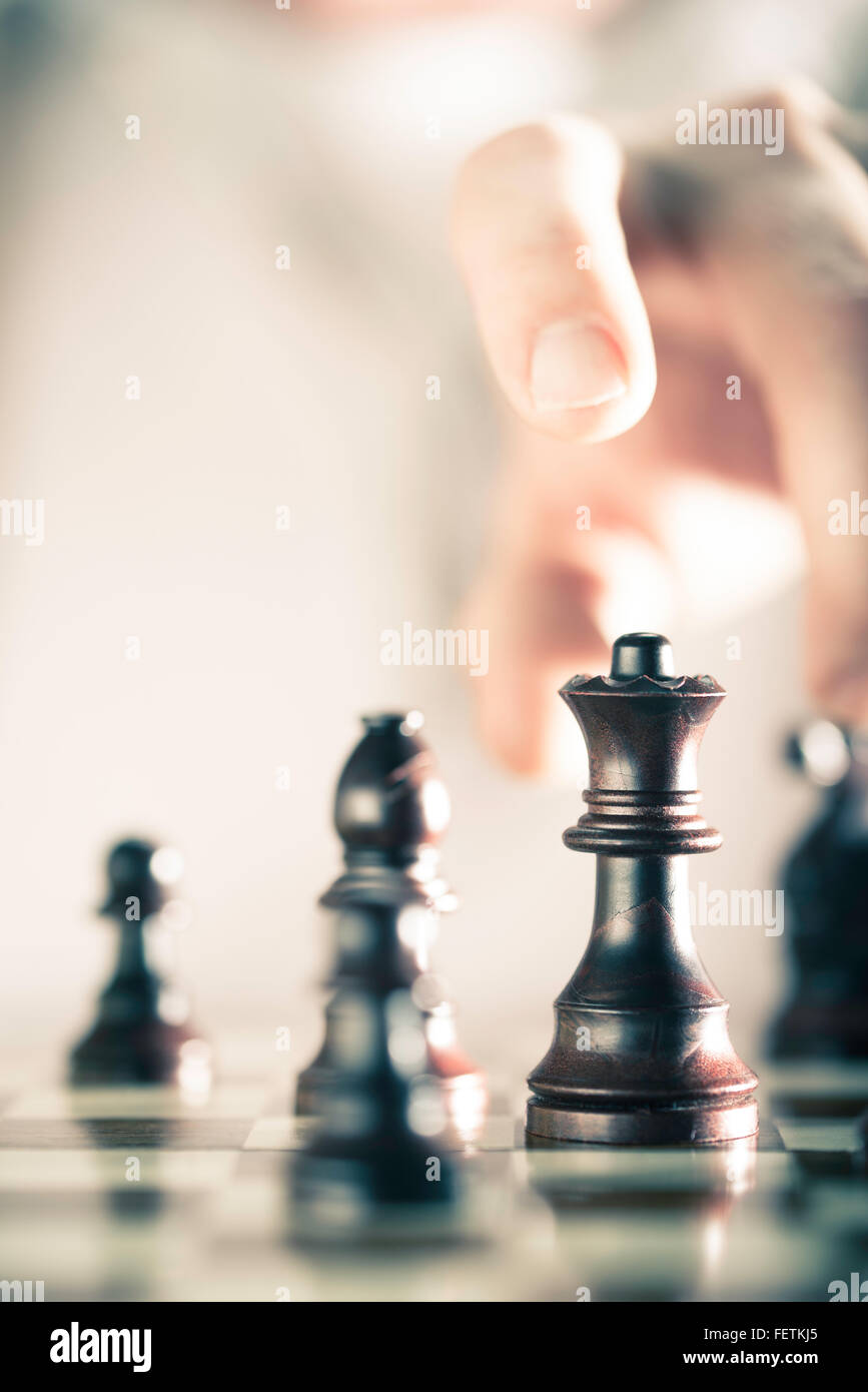 Vertical Image of a chess game with focus on the queen and a blurry hand at the background, Copy space on the left - Stock Image