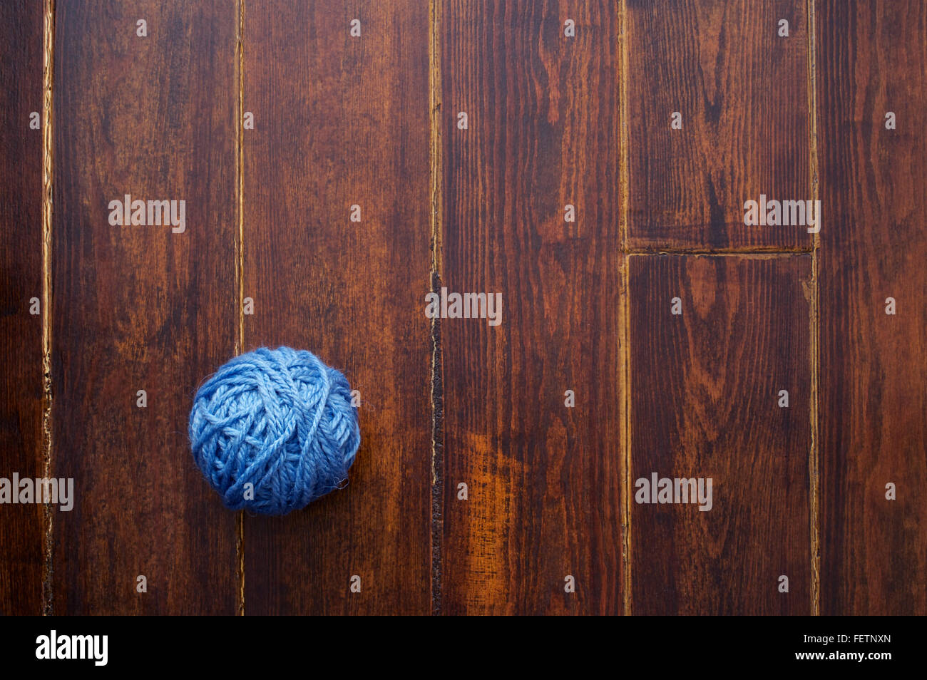 Blue skein over wooden brown striped table - Stock Image