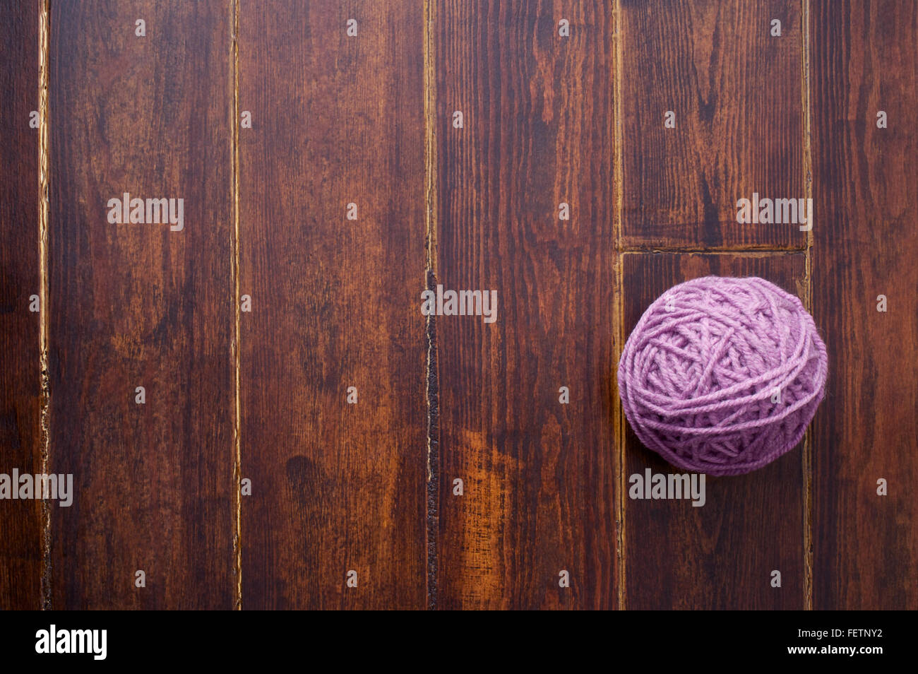 Lilac skein over wooden brown striped table - Stock Image