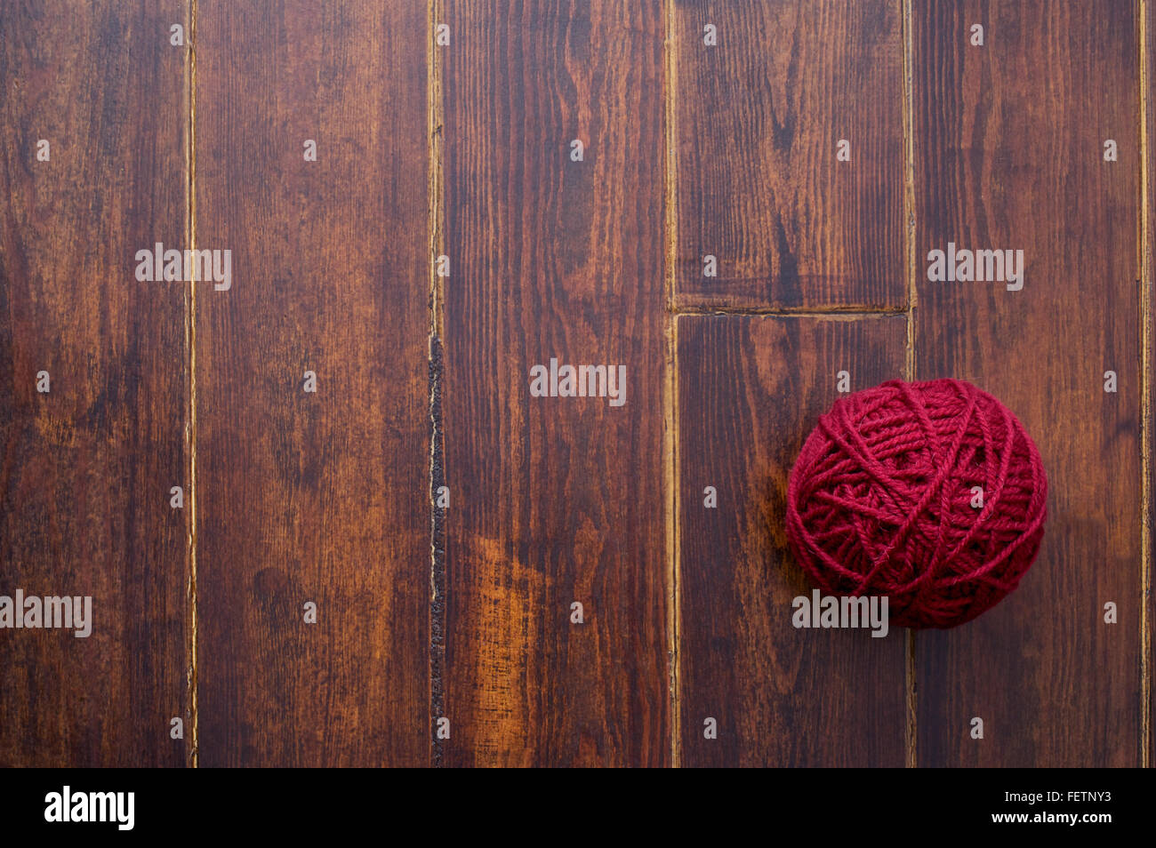 Red skein over wooden brown striped table - Stock Image