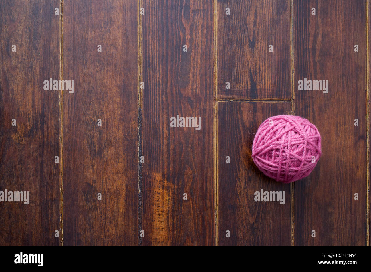 Pink skein over wooden brown striped table - Stock Image