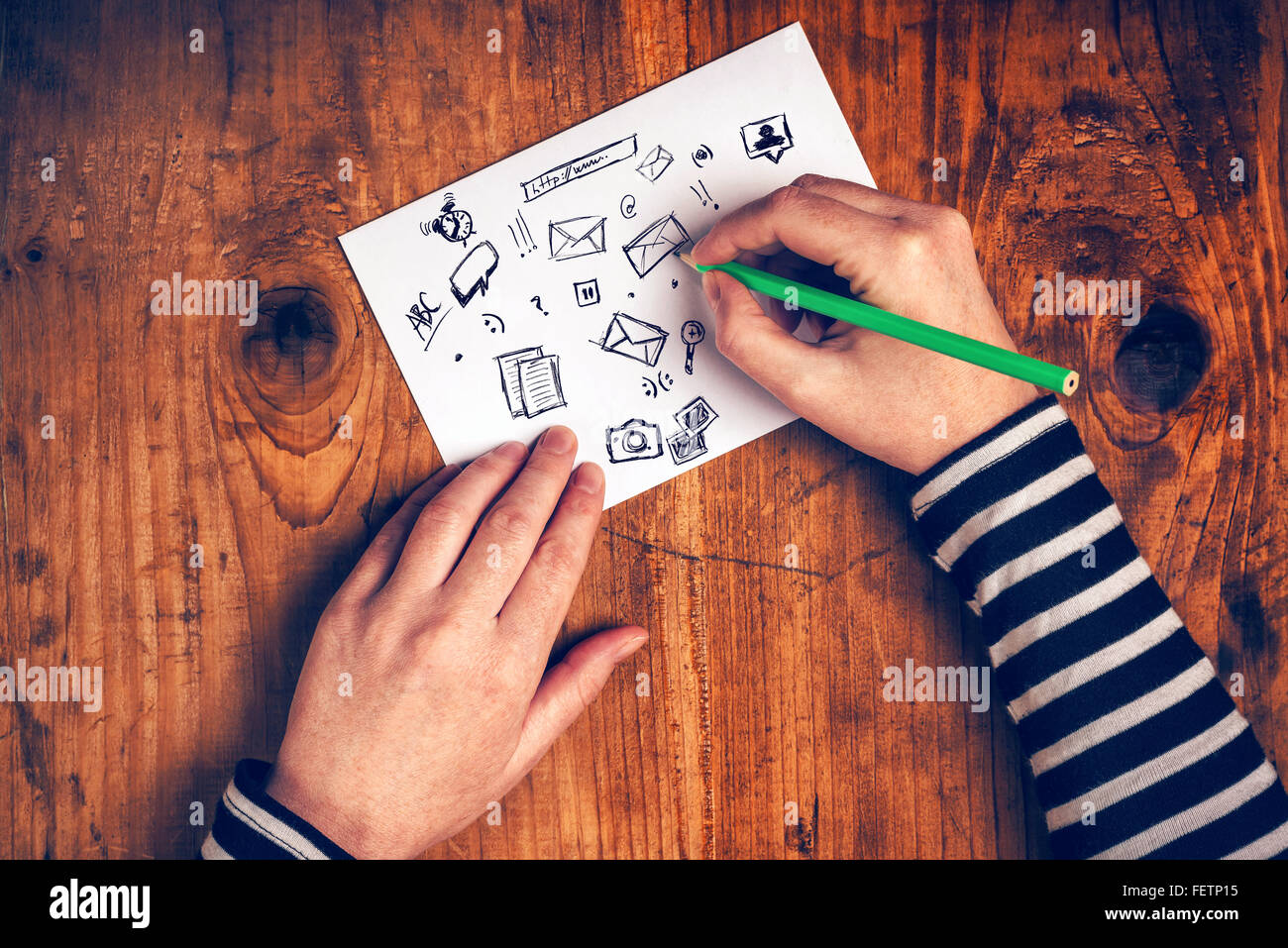 Female graphic designer sketching software icons on paper, top view, retro toned. - Stock Image