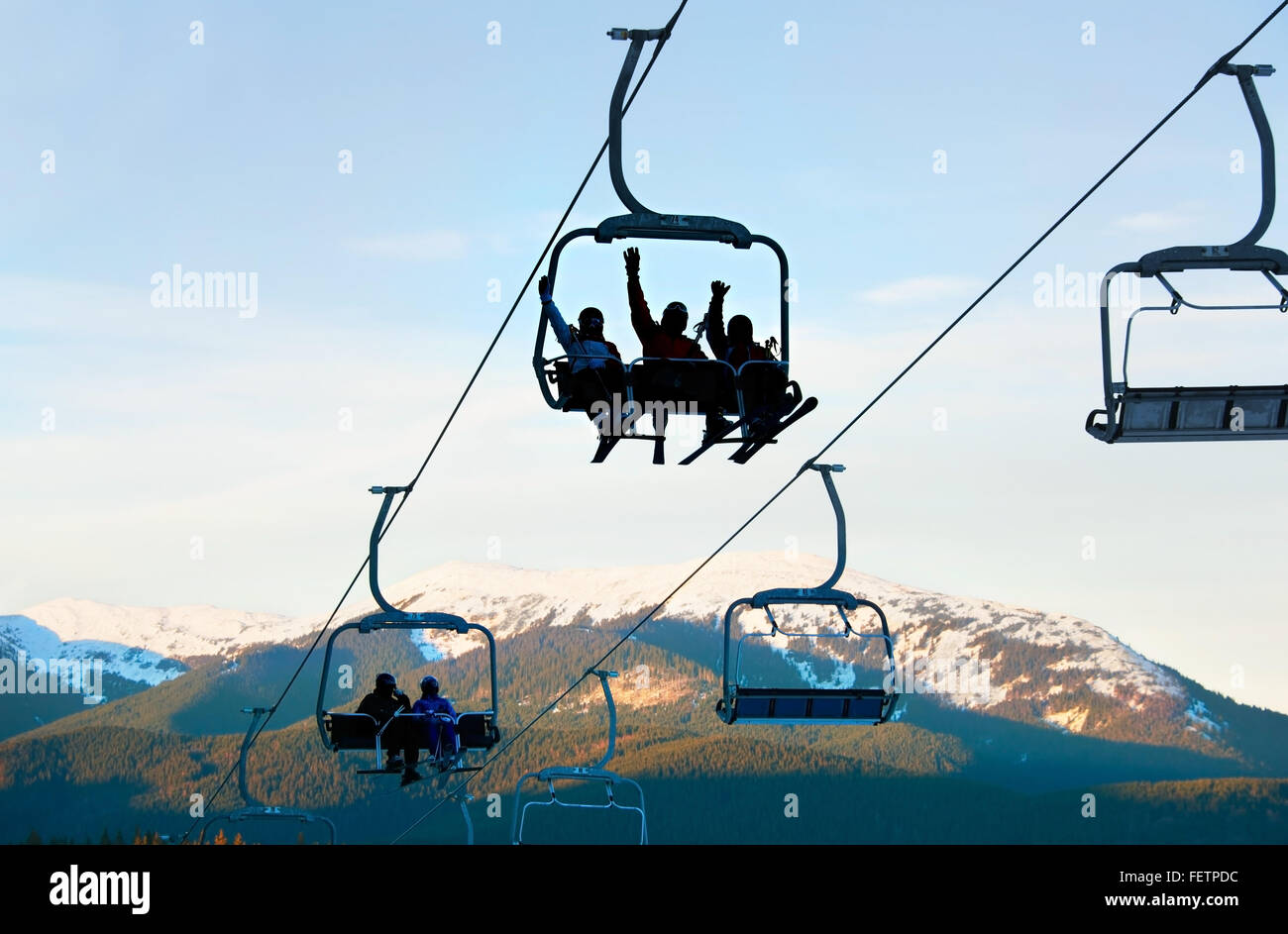 Silhouette of a group of people on a cableway at ski resort. - Stock Image