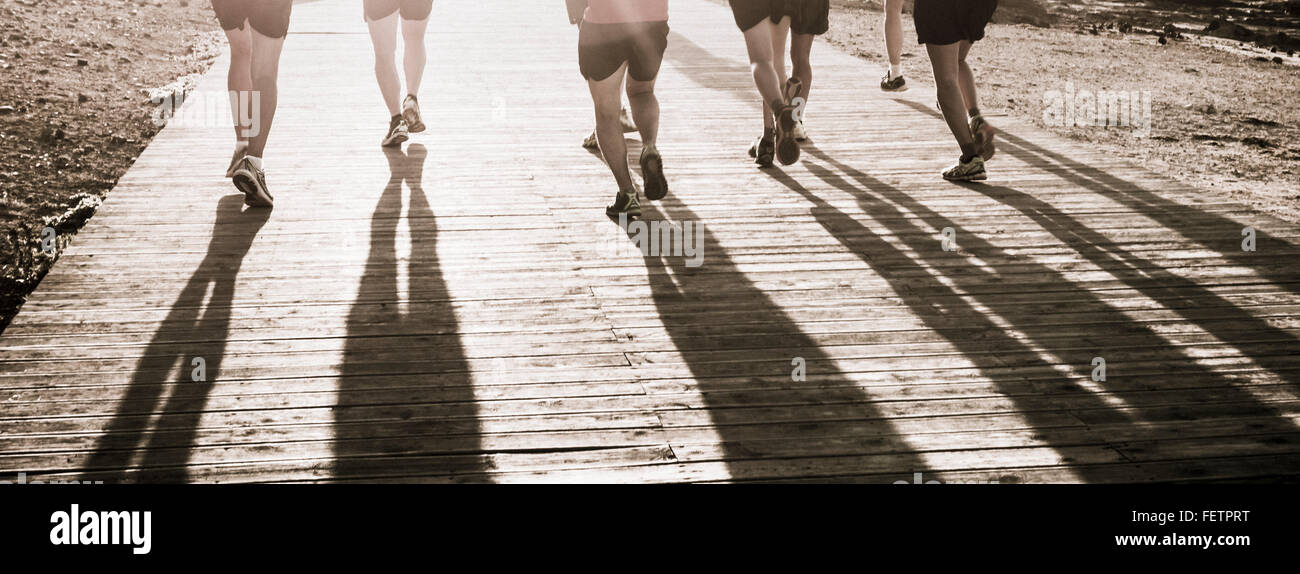 Group of joggers on wooden boardwalk - Stock Image