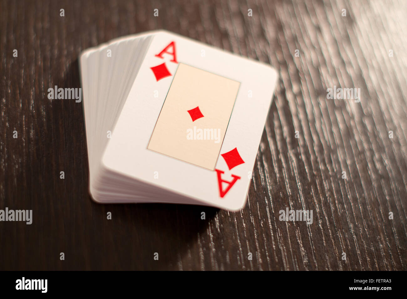 Stacked deck of playing cards showing the ace of diamonds on the top on a textured wooden table with back light - Stock Image