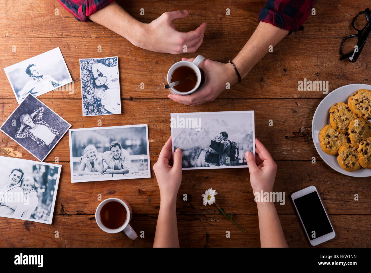 Mans and womans hands. Black-and-white photos. Couple. Tea, cookies, phone. Stock Photo