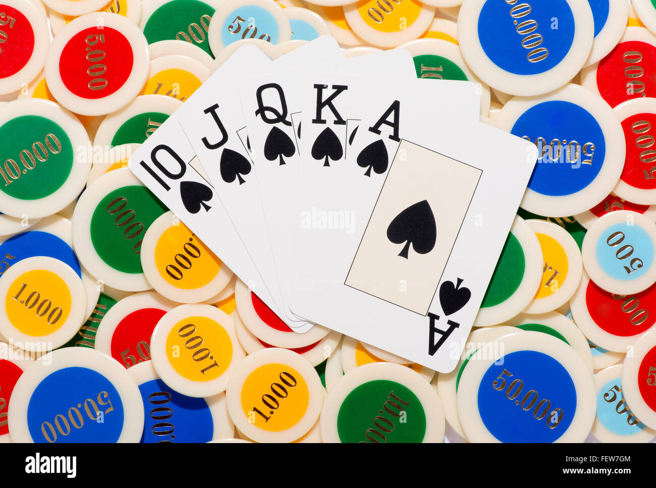 Poker hand with a straight flush in spades fanned over a colorful background of poker chips - Stock Image
