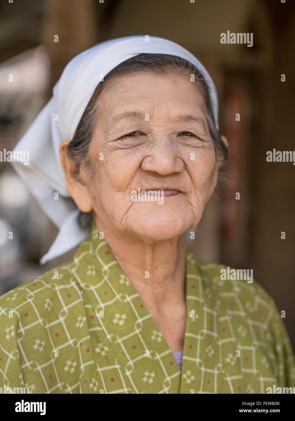 Elderly Okinawan woman wearing traditional clothing, Ryukyu Mura, Okinawa. Okinawan women have very long life expectancy - Stock Image