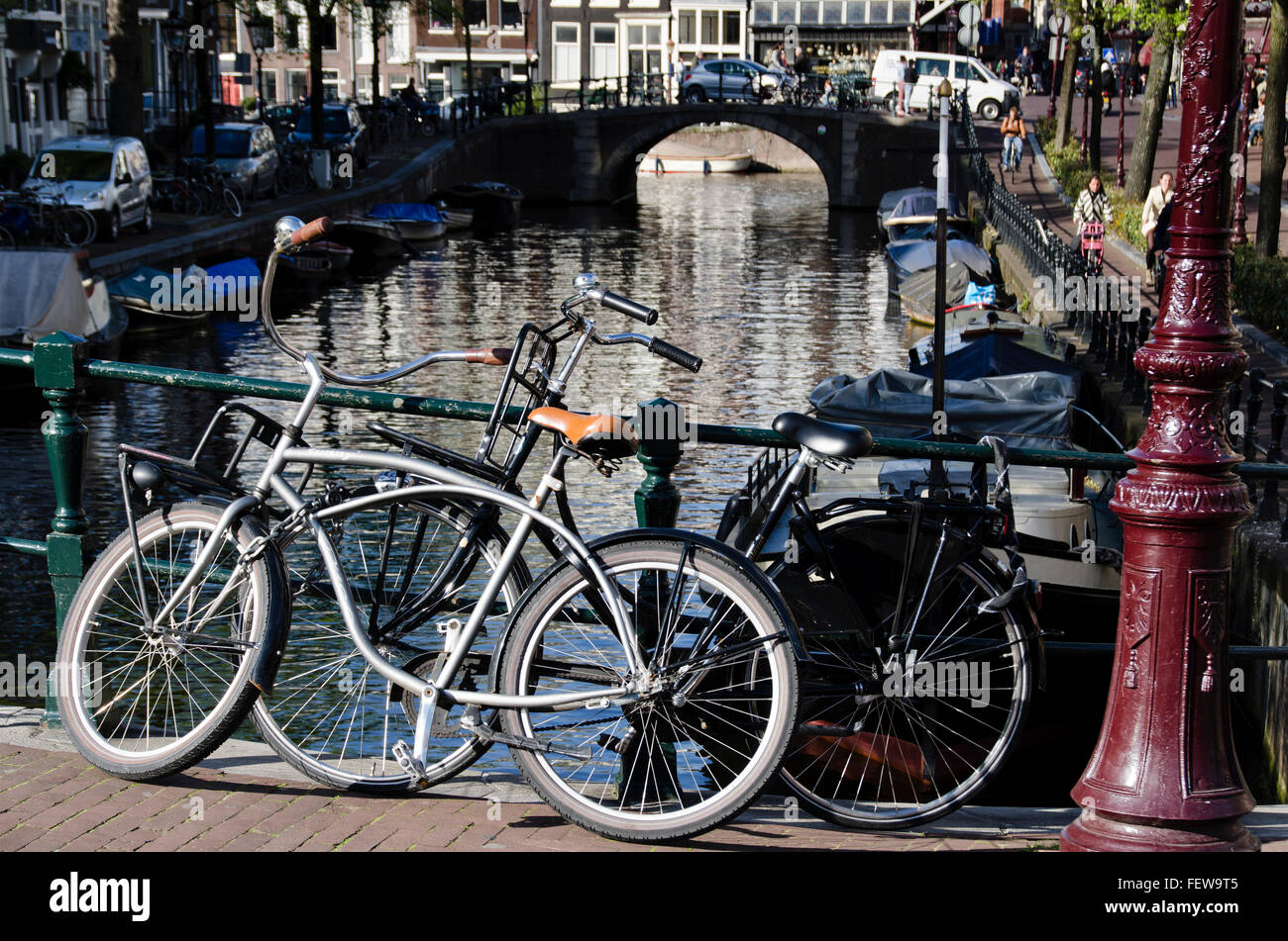 Amsterdam, Holland, Canal - May 7, 2016: two bikes on bridge over canal - Stock Image