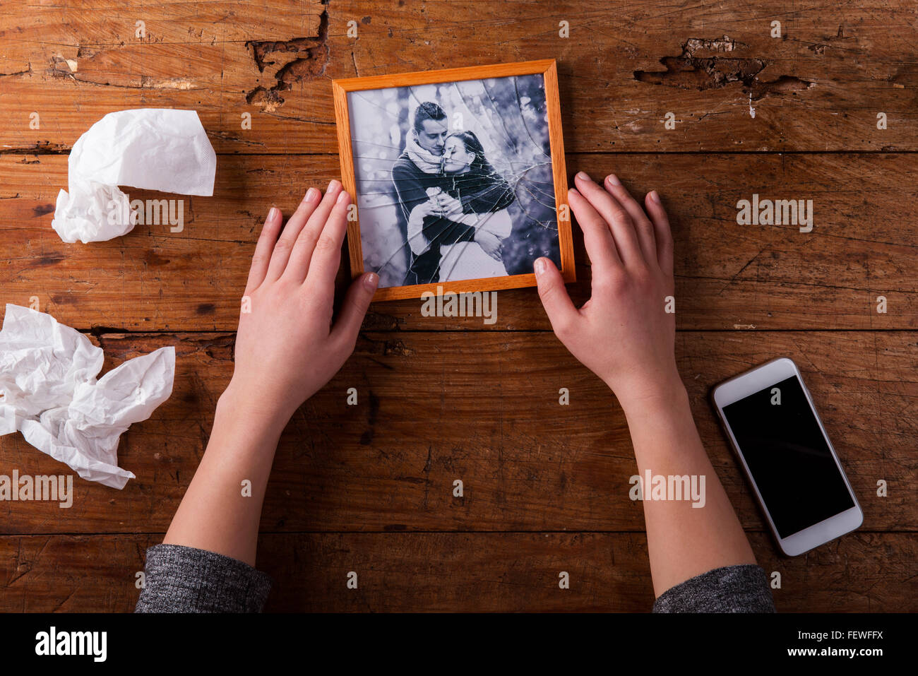 Unrecognizable sad woman holding broken picture of couple in love. - Stock Image