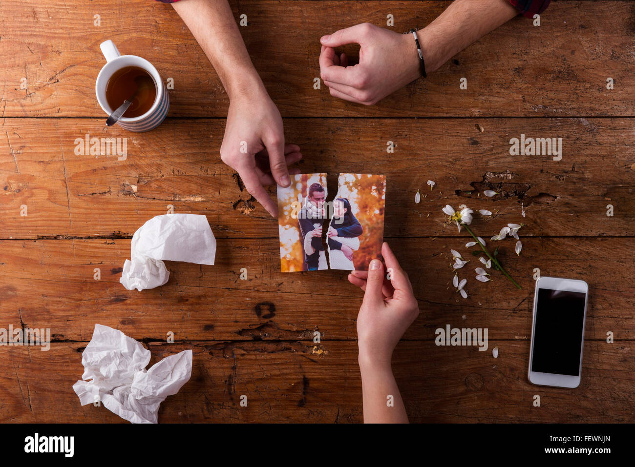 Sad mans, womans hands holding torn picture of romantic couple. - Stock Image