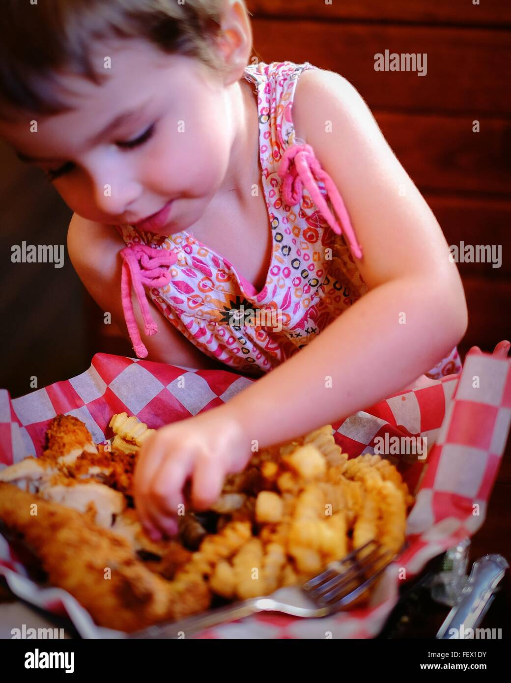 Cute Girl Having Chicken Fingers At Restaurant - Stock Image