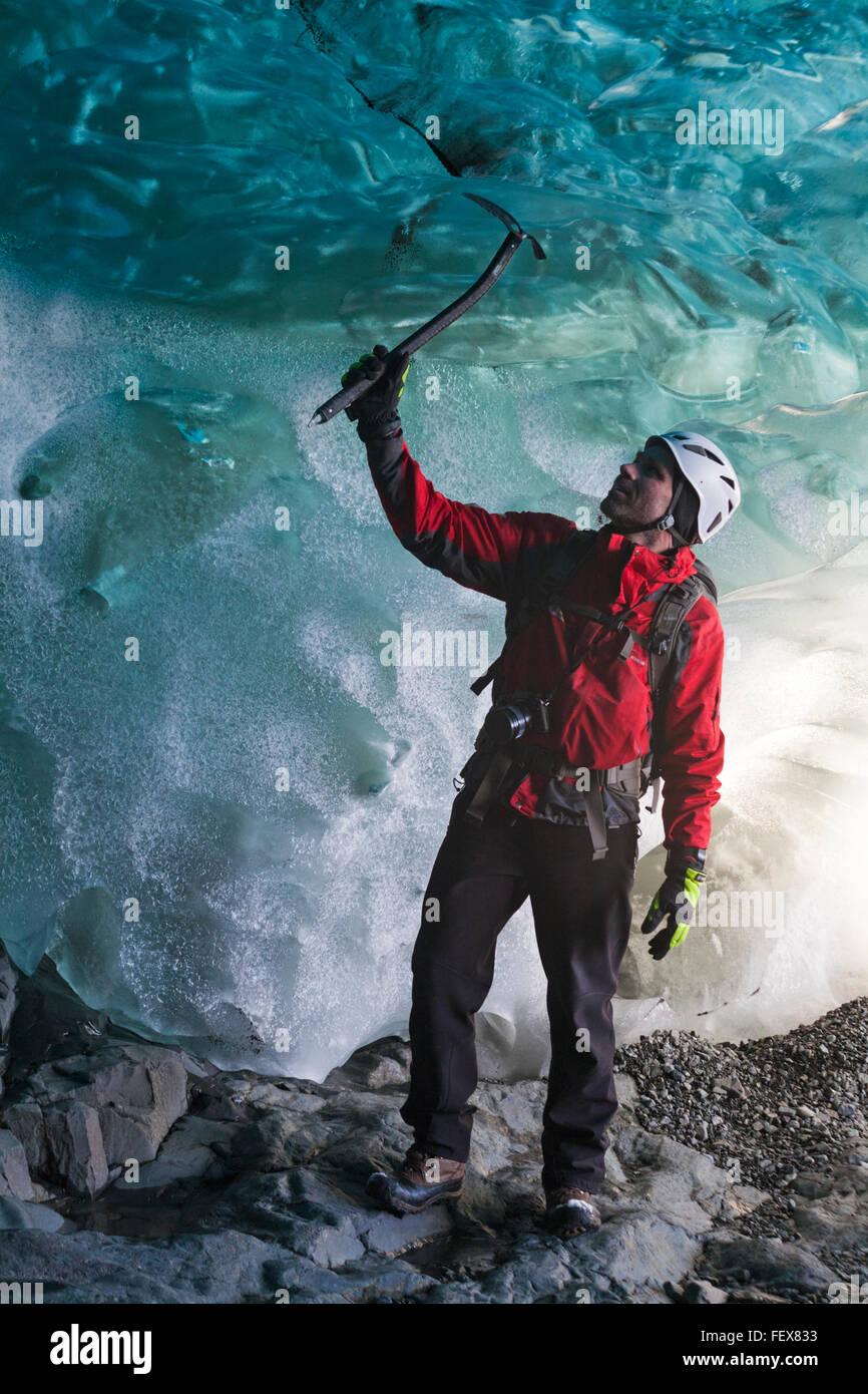 Ice climber in ice cave at Breidamerkurjokull Breiðamerkurjökull Ice Cave, Crystal Cave in Vatnajökull National Stock Photo