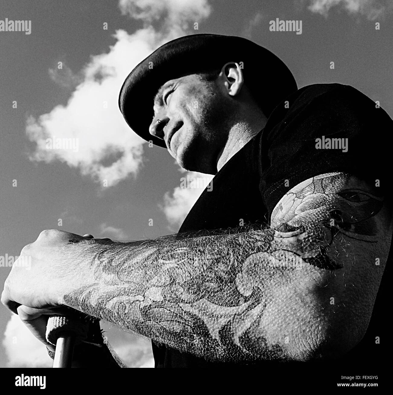 Low Angle View Of Young Man With Tattoo On Arm Against Sky - Stock Image