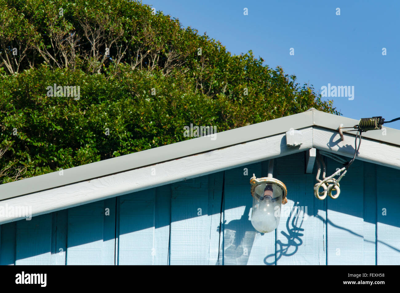 An old outdoor ketch yacht light on a blue timber building - Stock Image