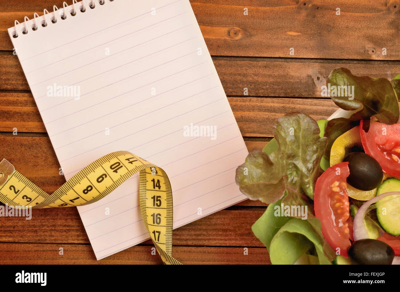 Notepad with centimeter and vegetable salad - Stock Image