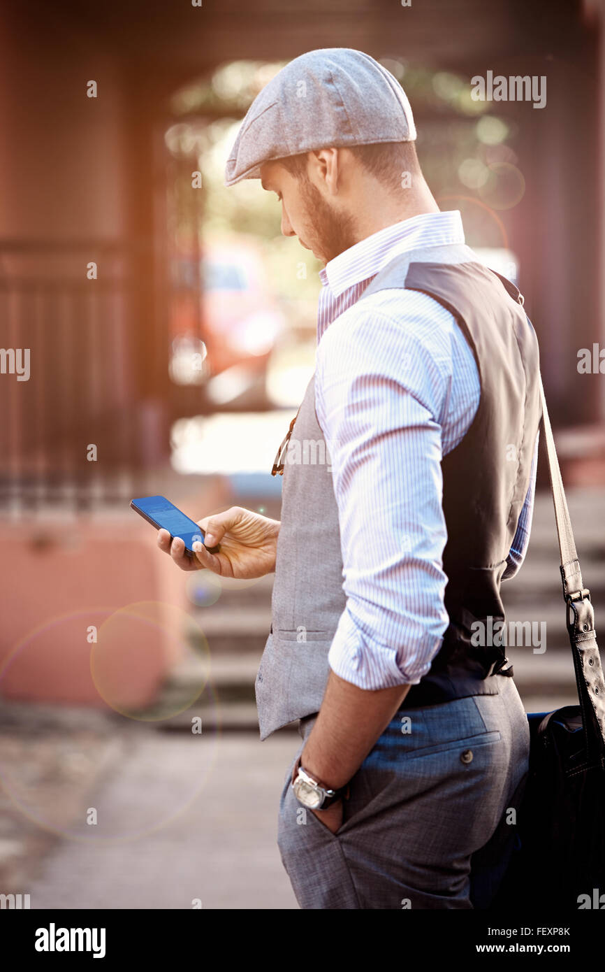 Young urban businessman professional on smartphone walking in street using app texting sms message on smartphone - Stock Image