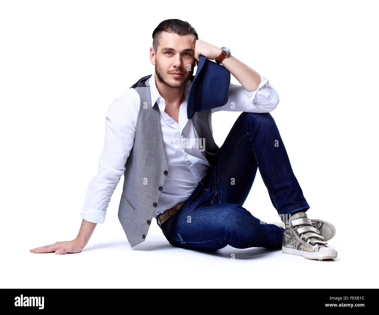 young casual man posing on the floor and smiling to the camera, against white background - Stock Image
